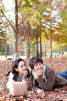 Young Couple Using Digital Tablet In Autumn