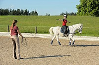 Young rider on a white pony getting a lunge lesson with arm raised sidewards, a lesson in balancing