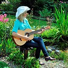 woman in the garden play the guitar