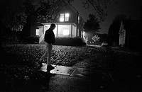 Man Walking Past House at Night