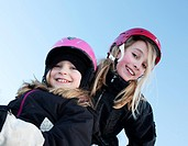 Portrait of two sisters wearing ski helmets