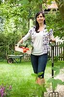 Woman carrying fresh veggies in garden