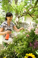 Woman spraying plants in the garden