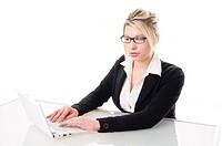 Junge attraktive Frau Studentin, Geschäftsfrau im dunklen Blazer sitzt am Schreibtisch und arbeitet an ihrem Laptop und ist nachdenklich, isoliert vor...