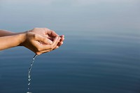 Cupped hands holding water from lake