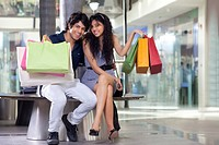 Handsome young couple showing shopping bags at mall