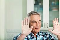 Germany, Berlin, Senior man showing handful of flour, portrait