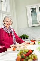 Germany, Berlin, Senior woman preparing food, smiling, portrait