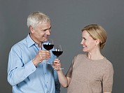 Mature couple with wine, smiling