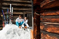 Austria, Salzburg, Young couple sitting in front of alpine hut