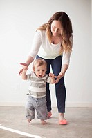 Young mother assisting baby boy 6_11 months in first steps