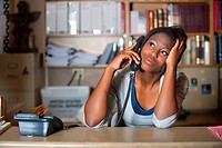 USA, Texas, Young woman having conversation in office