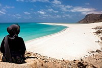 A tourist sitting on a top rock viewing the sand bar on the seaward edge of Ditwah lagoon near Qalansiyah, Socotra island, listed as World Heritage by...