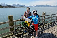 Two cyclists with electric bicycles studying a map on the pier of Chieming, Chiemsee lake, Chiemgau region, Upper Bavaria, Bavaria, Germany, Europe