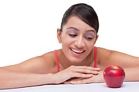 Beautiful young woman staring at red apple over white background