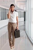 Full length of businesswoman on phone call at office