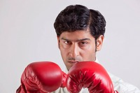 Close_up portrait of businessman wearing boxing gloves