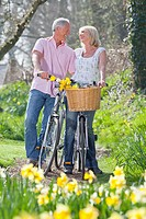 Smiling senior couple with bicycles face to face in sunny garden with daffodils