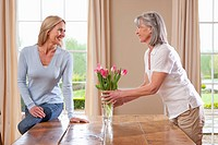 Mother and daughter arranging tulips in vase on dining room table