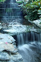 Waterfall over the green rock and garden