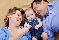 Mixed Race Family with Baby Boy Playing on the Blanket