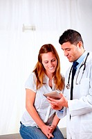 Handsome doctor and a patient looking to tablet PC