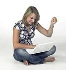 successful computing girl sitting in light back