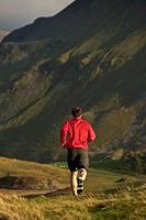 Man running on rural mountain road