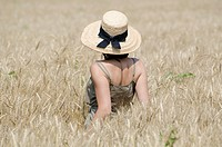 Woman with a straw hat standing up in the wheat field
