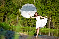 Happy romantic woman with parasol in sunlight