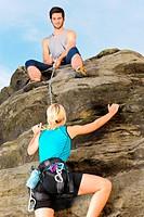 Woman climbing up rock man hold rope