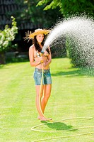 Summer garden woman play with water hose