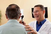 Audiologist doing an ear canal inspection of a patient