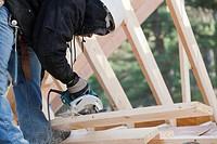 Carpenter using a circular saw making bevel cut
