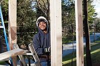 Carpenter climbing ladder to upper level