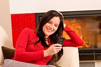 Fireplace woman with phone lying home sofa