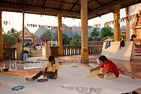 Craftspeople painting ceiling panels on the floor of a Buddhist temple, Vang Vieng, Laos, Southeast Asia