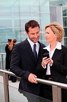 Businessman and businesswoman watching mobile phone outdoors