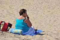 Fat sunbather in summer eating ice cream on beach along the North Sea coast at Koksijde / Coxyde, Belgium