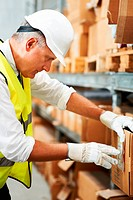 Mature male supervisor inspects the barcodes on a box of his stock wearing white gloves