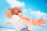 Portrait of playful mature couple having piggyback ride with arms outstretched outdoors