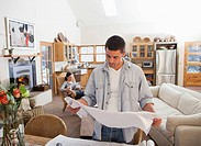 Man in living room looking at blueprints