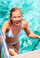 Portrait of sexy young woman in the pool smiling to you