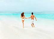 Rear view of an energetic, fit couple splashing in the ocean shallows hand in hand