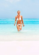 Portrait of sexy young woman enjoying while walking in water at beach