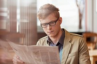 Man reading a newspaper in a restaurant