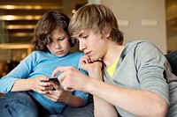 Teenage boy with his brother using a cellphone
