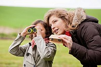Boy looking through binoculars standing with his mother
