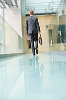 Rear view of a businessman walking in an office corridor