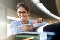 Portrait of smiling businessman leaning on car